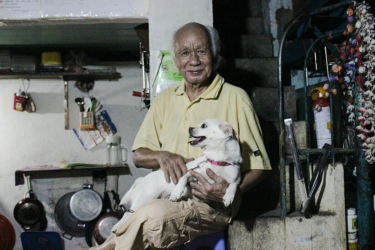 Căn bếp chung trong nhà là nơi mọi người trong thường vừa nấu ăn, giặt đồ và buôn chuyện cùng ông. Ban ngày nhà vắng người, ông bầu bạn với chú chó đã nuôi 6 năm của mình. Ảnh: Diệp Phan.