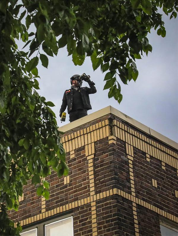 Một thành viên của đội tự quản nhìn ra từ mái nhà ra xung quanh bằng ống nhòm, hôm 2/6. Ảnh: AP.