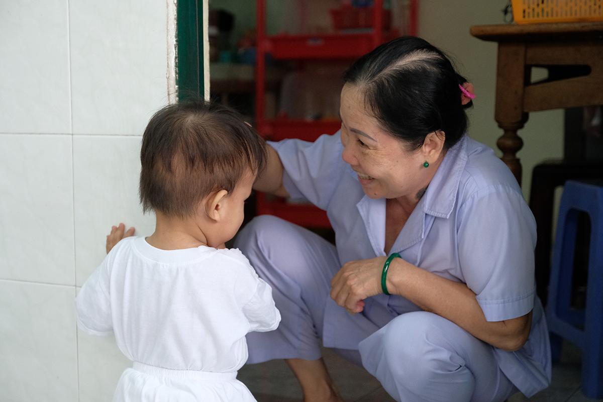 Cô Nguyễn Thị Nguyên đang chơi đùa với một bé tại khoa Sơ sinh. Ảnh: Phương Phương