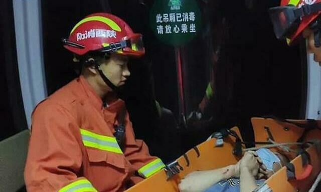 Ông Hoàng nằm trên cáng cảm ơn đội cứu hộ đã không quản vất vả để cứu sống mình. Ảnh:sznews.