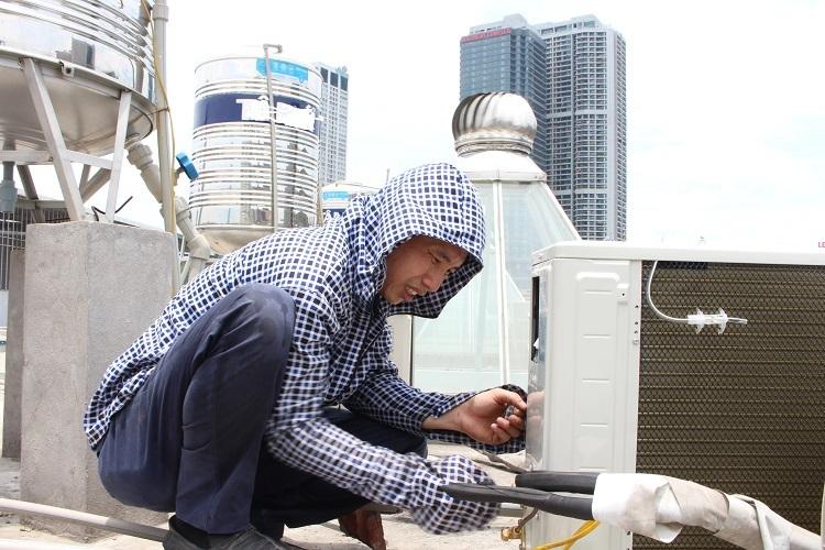 Anh Xuân lắp dây đồng vào cục nóng điều hòa trên sân thượng tầng 4. Nhiệt độ ngoài trời chạm ngưỡng 40 độ C. Ảnh: Phạm Nga.