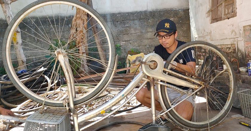 Anh Trần Quyết Thắng sửa xe tại căn nhà nhỏ của gia đình sáng 24/6. Ảnh: Phú Sơn.