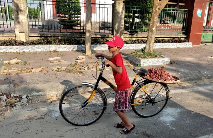 Bé Bảo Khánh với chiếc xe được tặng đi bán hoa quả sau buổi học. Ảnh: Quyết Thắng.