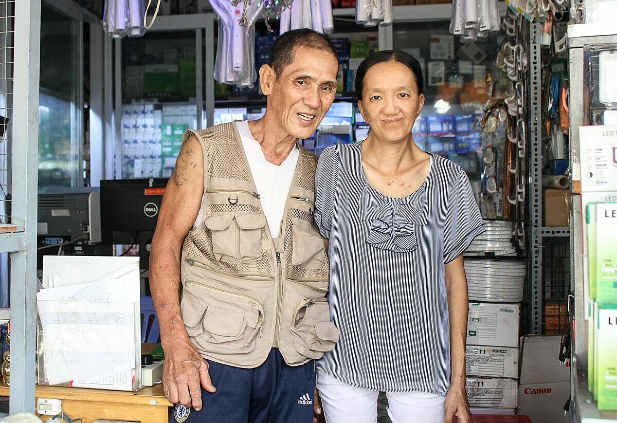 Vợ ông Toàn đang phụ bán cho cửa hàng đồ điện trước nhà. Ảnh: Diệp Phan.