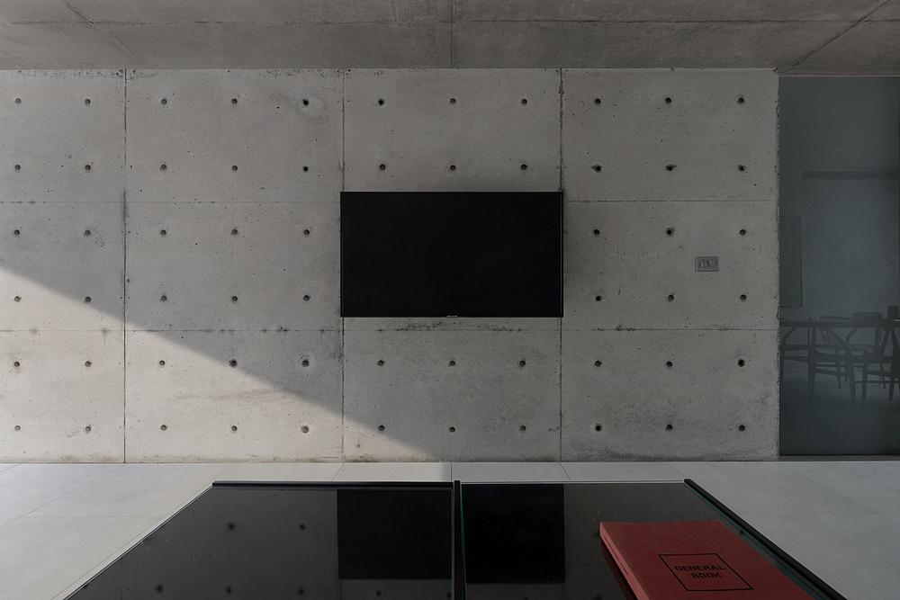 Bức tường bê tông cao 2,2 m ngăn không gian sinh hoạt chung với phòng làm việc, phòng ngủ và phòng vệ sinh. Ảnh: Triệu Chiến.