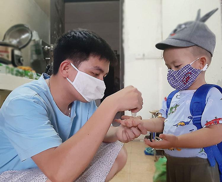 Lo ngại dịch bệnh bùng phát, anh Hùng rửa tay bằng gel trước khi đưa con trai đến lớp. Ảnh: Nhân vật cung cấp.