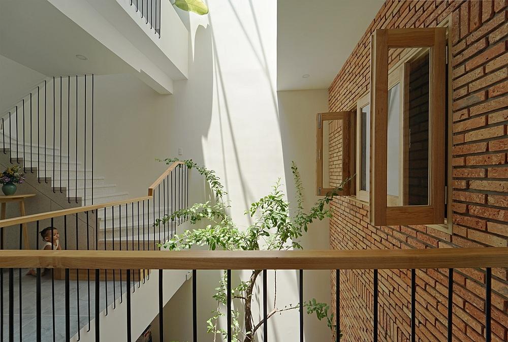 Tường gạch phân tách không gian và dịu bớt độ chói sáng của khoảng giếng trời trên mái. Ảnh: Nguyễn Cường.