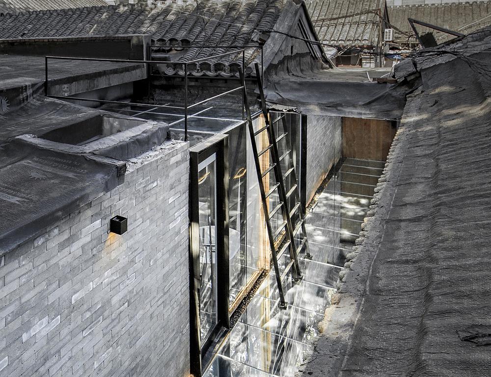 Ngôi nhà sau cải tạo vẫn giữ lại một mái ngói song thêm vào các tấm gương và tường kính. Ảnh: Weiqi Jin.