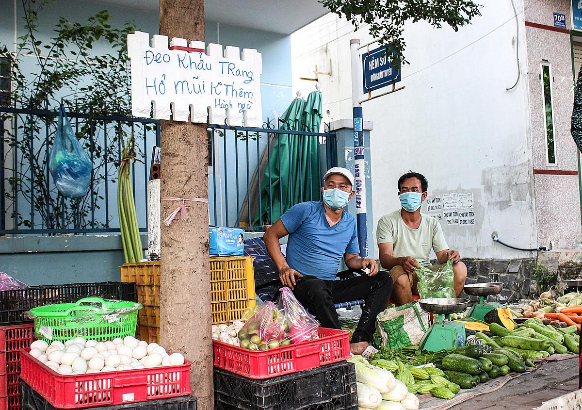 Anh Minh (bên trái) treo những câu nhắc nhở khách đeo khẩu trang ở sạp rau của mình. Ảnh: Diệp Phan.