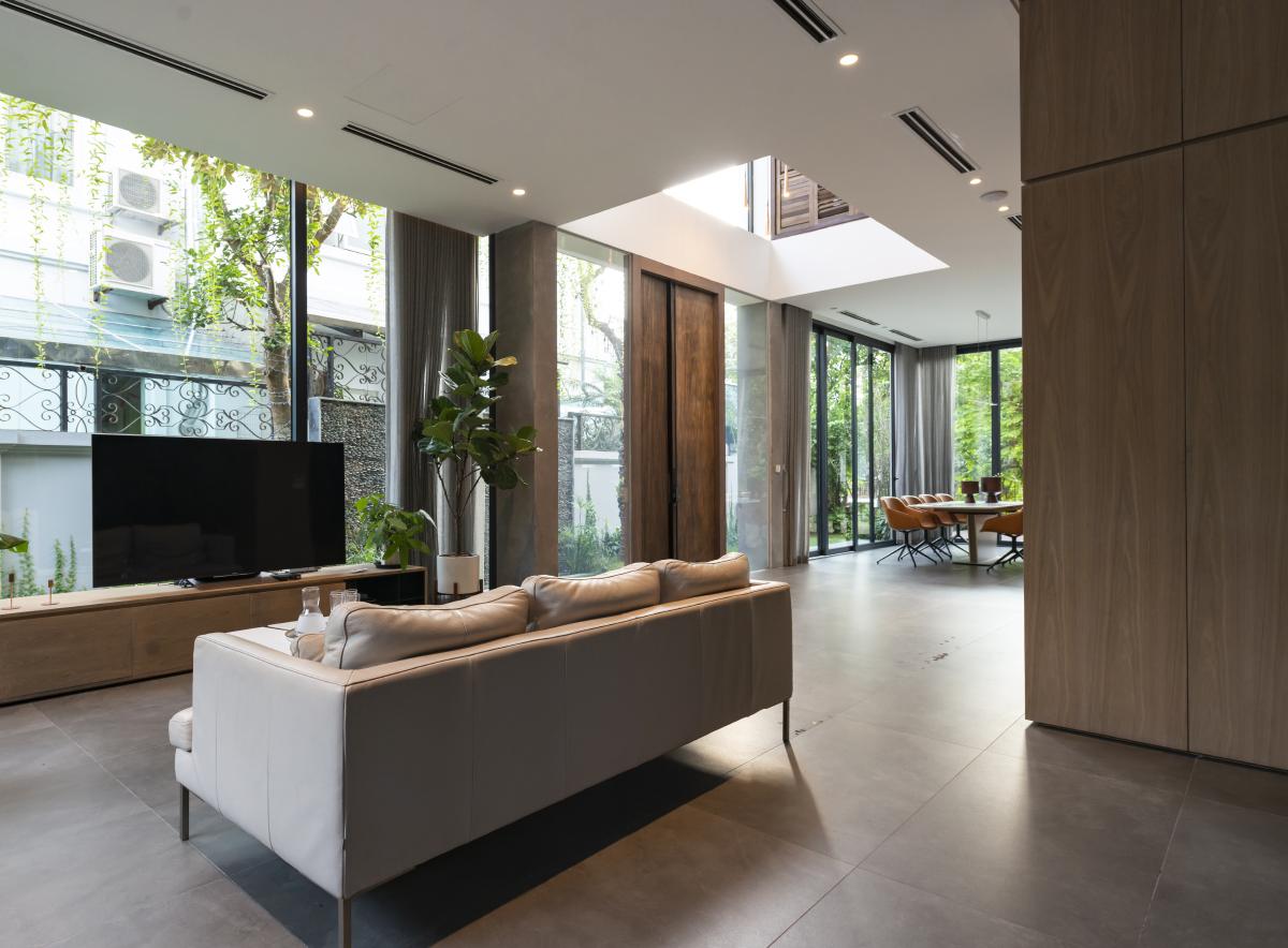Phòng khách thông với phòng ăn, đều hướng nhìn ra khu vườn quanh nhà. Ảnh: NGHIA Architect.