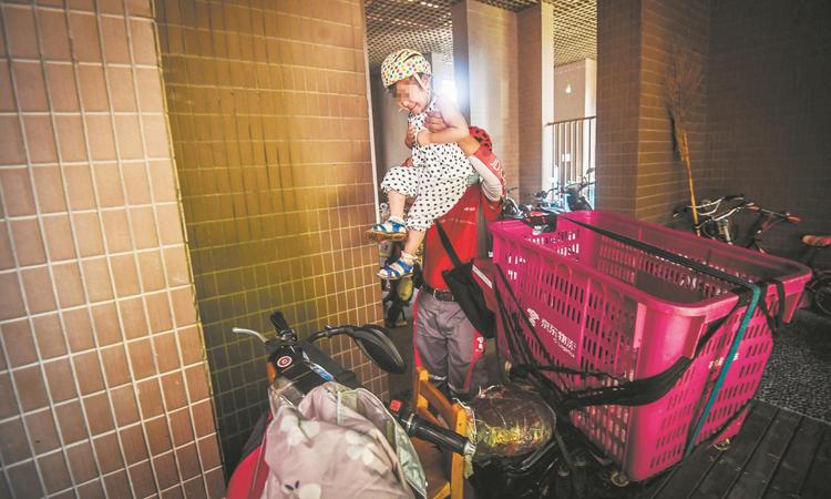 Đồng Đồng được bố đưa đi làm cùng nhiều tháng nay. Cô bé được đặt vào chiếc ghế được gắn phía trước xe máy. Mỗi khi đưa hàng, Dương Bích thường buộc con gái vào một chiếc túi đeo trước ngực. Ảnh: The paper.