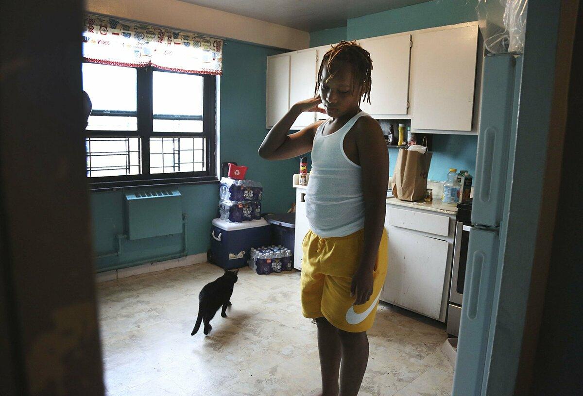 Mason Washington đứng trước tủ lạnh gia đình sau khi lùng tìm đồ ăn cho buổi sáng. Ảnh: Jessie Wardarski/AP.