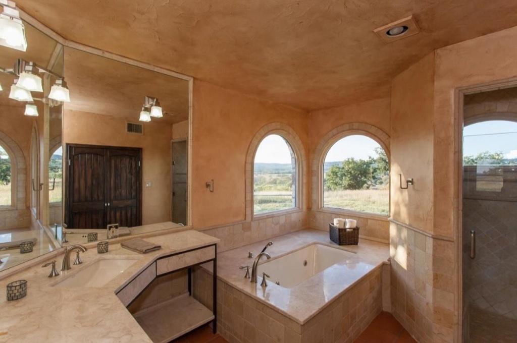 Không gian có bồn tắm, phân khu vực vệ sinh, tắm riêng. Những ô cửa sổ hình vòm phong cách Địa Trung Hải, tạo điểm nhấn cho căn phòng, giúp đón ánh sáng tự nhiên.