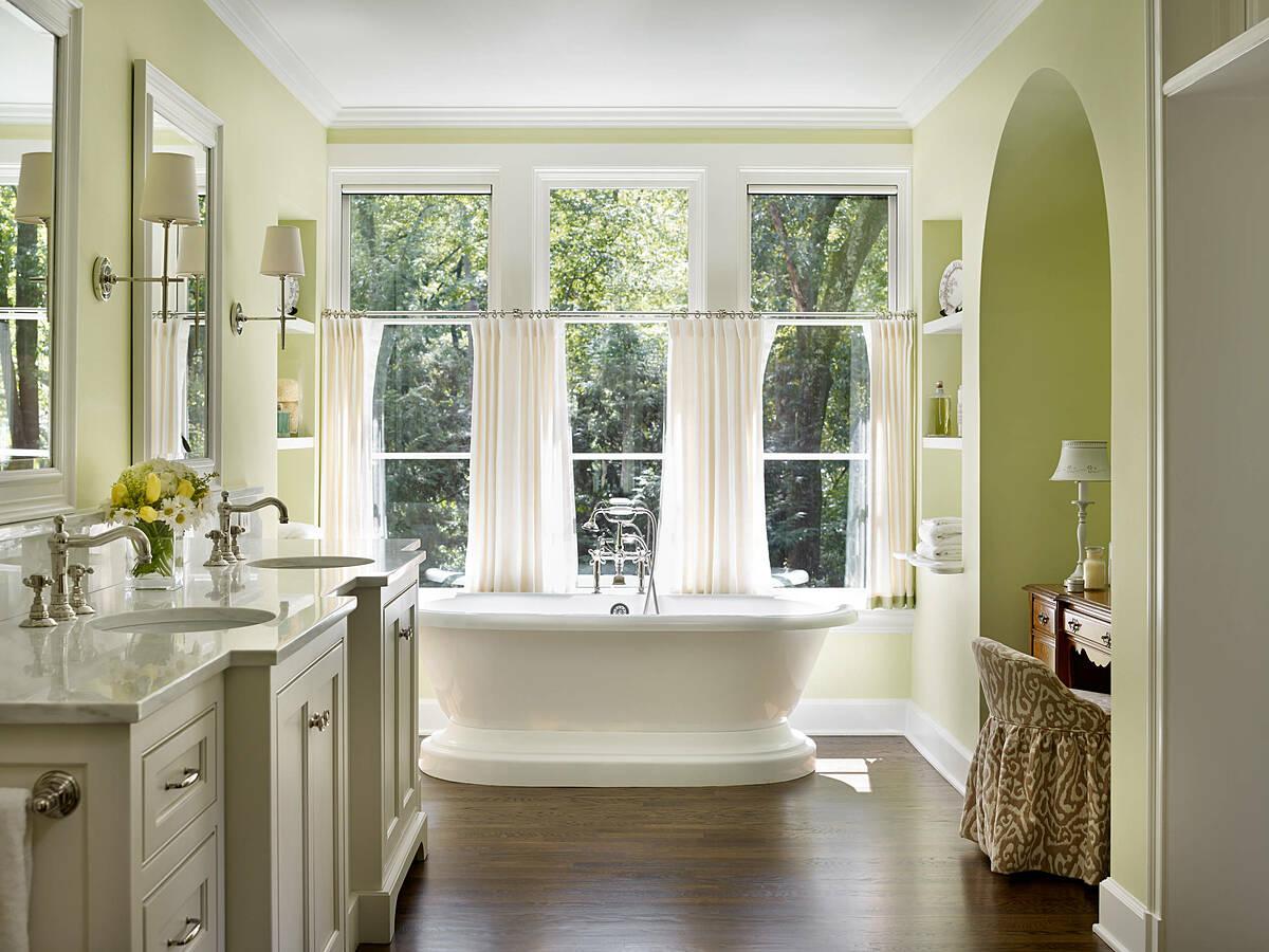 Những tấm rèm trắng đem đến cảm giác thanh lịch, yên bình, giúp ngăn chặn tia nắng mặt trời. Cửa sổ kết nối với thiên nhiên, sàn gỗ giúp phòng tắm ấm áp, sang trọng.