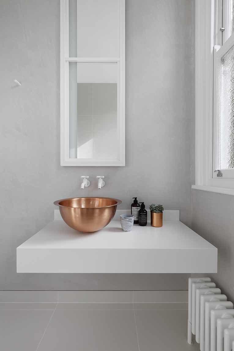 Trong phòng tắm tối giản, đơn sắc, chủ nhà có thể tạo điểm nhấn với bồn rửa màu đồng, nổi bật trên nền xám, trắng. Ảnh: Alexander James