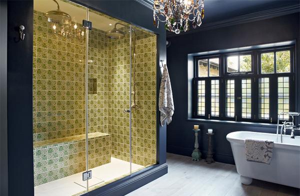 Bức tường màu xanh tím than kết hợp với gạch vàng ở khu vực tắm tạo nên sự đồng nhất. Không gian thoáng đoãng với hệ thống cửa hộ bằng kính, thuận lợi đón ánh sáng mặt trời, gia chủ có thể ngắm khung cảnh thiên nhiên khi ngâm mình thư giãn trong bồn tắm.