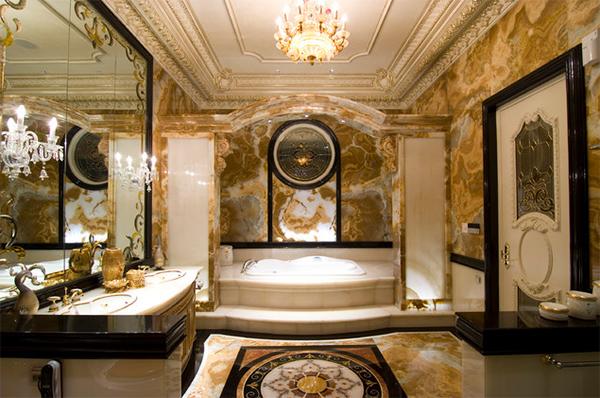Trong ảnh là phòng tắm phong cách cổ điển, sang trọng, tường nhà màu trắng xen sắc vàng, thiết bị nội thất màu đồng. Bên cạnh đó, gia chủ bố trí hệ thống đèn chiếu sáng cùng tông màu khiến không gian trở thành một tổng thể thống nhất.
