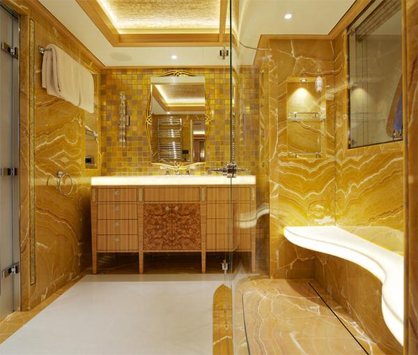 Một phòng tắm nhỏ, màu vàng bố trí ở khắp mọi nơi từ gương, đèn chiếu sáng, tủ đựng đồ.