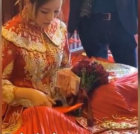 Cô dâu ngang nhiên ngồi đếm tiền nhà trai mang đến trước mặt quan khách. Ảnh: Aboluowang.