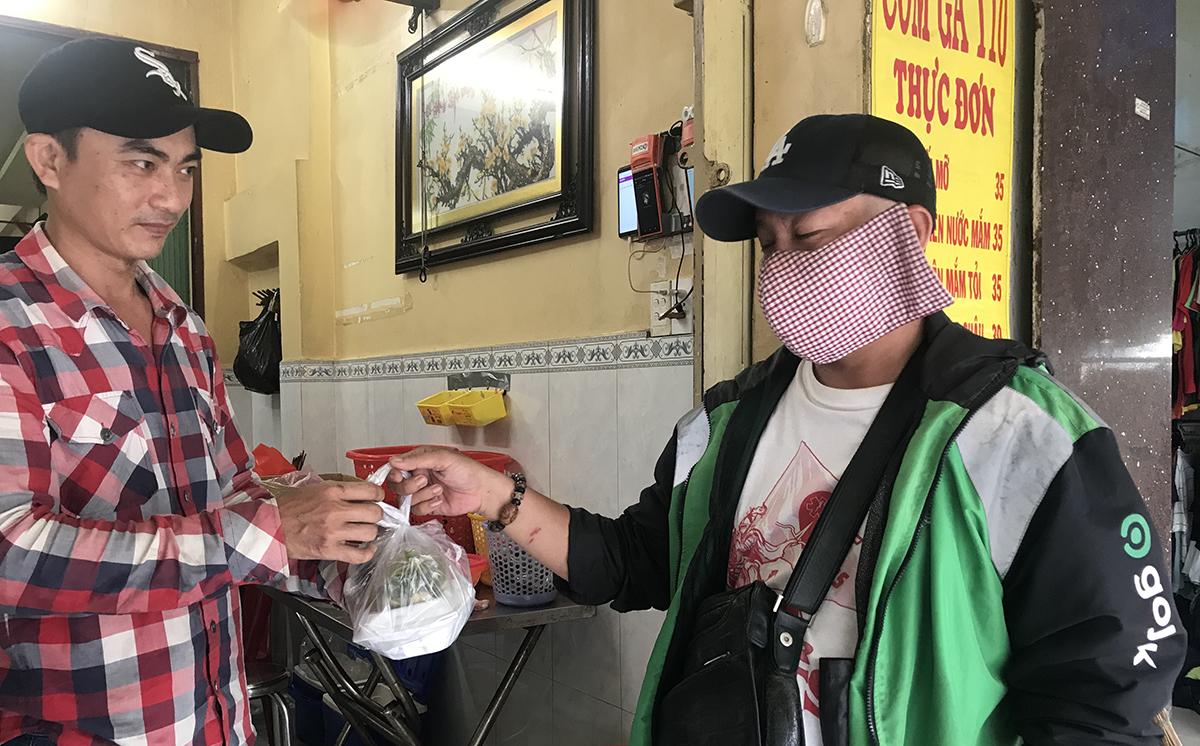 Anh Thường giao cơm cho tài xế Gojek trong chiều 12/10. Ảnh: Hoàng Anh