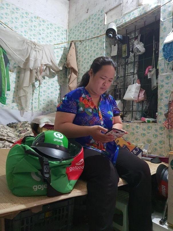 Sau một ngày làm việc, chị Liên tính lại số đơn hàng nhận, tổng thu nhập rồi xem những video ca nhạc trên mạng trước khi đi ngủ. Ảnh: Nha Trang.