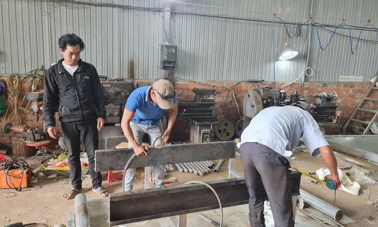 Nguyễn Kim Long (áo đen) hướng dẫn công nhân trong xưởng chế tạo máy phân loại cà chua. Ảnh: K.L
