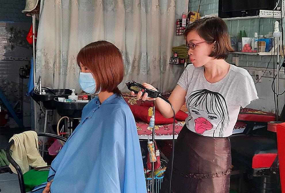 Với kiểu tóc cắt ngắn hoặc tóc tém người thợ phải dùng lược để cố định lớp tóc thường xuyên để cắt nên với chị Trâm đây là hai kiểu tóc khó. Tuy nhiên, chưa đầy 10 phút, chị đã cắt xong với sự kết hợp của tông đơ và kéo. Ảnh: Diệp Phan.