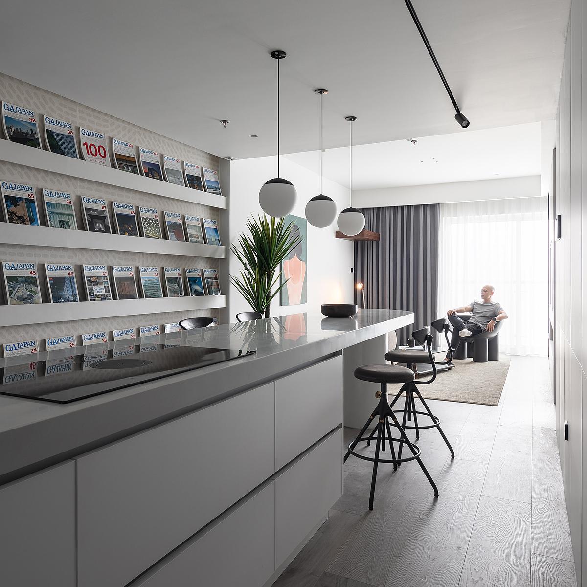 Đảo bếp kết hợp bàn ăn trở thành điểm nhấn cho công trình. Phía trước đảo bếp, kệ để tạp chí chạy từ cửa chính đến phòng khách đưa thêm màu sắc vào căn hộ toàn màu trắng. Ảnh: Thien Thach Photo.