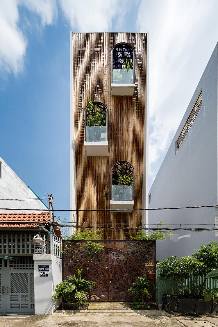 Mặt tiền căn nhà với lớp vỏ tre, cổng sắt tạo hình và những mảnh vườn lơ lửng khiến người đi qua dừng lại ngắm nghía. Ảnh: Quang Dam.