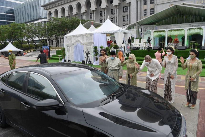 Gia đình cô dâu, chú rể chào khách lướt xe qua. Ảnh: Straitstimes.