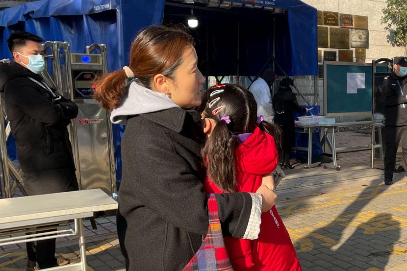 Bà mẹ an ủi con gái, trong khi bố phóng về nhà lấy căn cước công dân tại một điểm thi ở Thượng Hải hôm 19/12. Ảnh: Sixthtone.