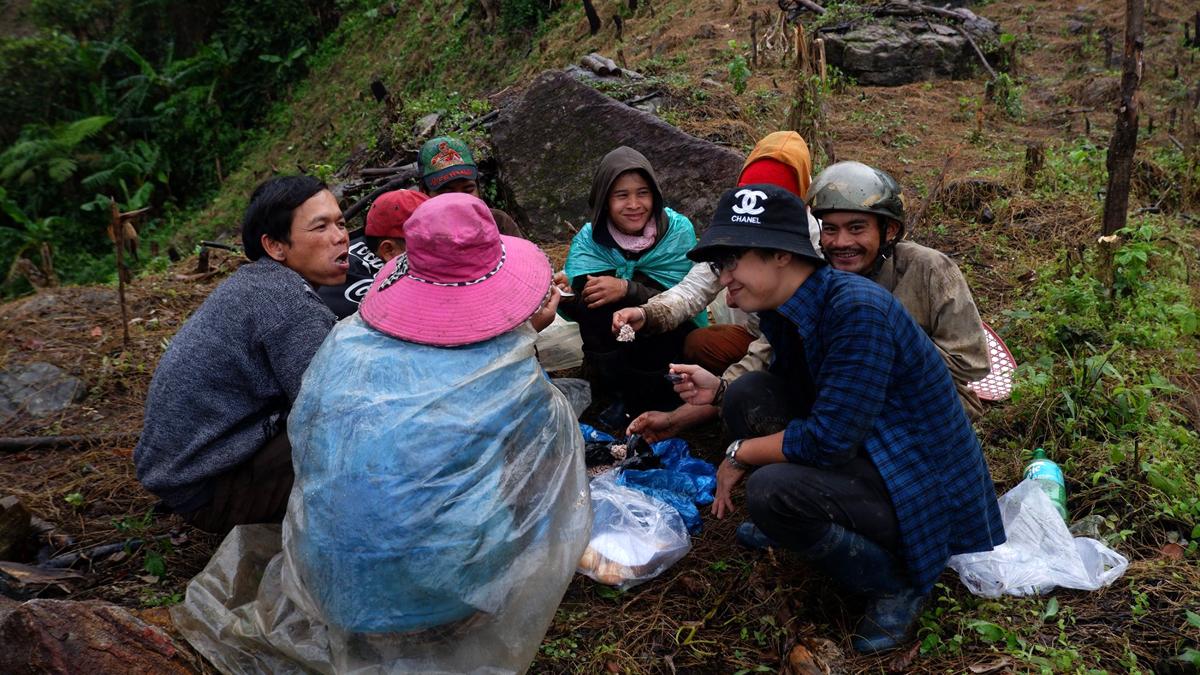 Tất Đạt (áo kẻ xanh) ăn trưa cùng người dân ở xã , sau một buổi thu hoạch sâm. Ảnh: Nhân vật cung cấp.