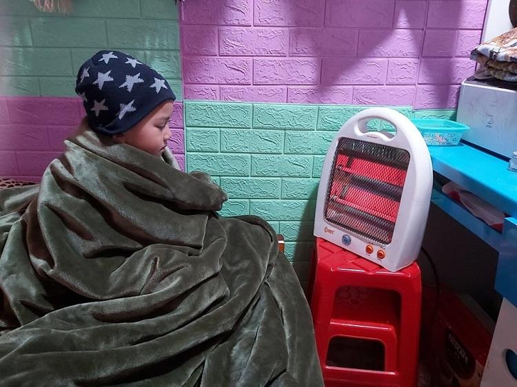 Con trai chị Thu Hiền co ro trong chăn xem điện thoại vì lạnh. Ảnh: Thu Hiền.