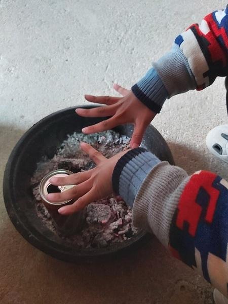 Thời tiết rét buốt, lại mất điện, chị Hiền phải mua than về để con sưởi. Chị đặt lon đựng nước vào để hút khí than và mở cửa để phòng thoáng, tránh ngộ độc. Ảnh: Thu Hiền.