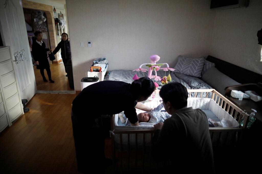 Một đôi vợ chồng Hàn Quốc chăm đứa con mới sinh. Ảnh: Kim Hong-Ji/Reuters.