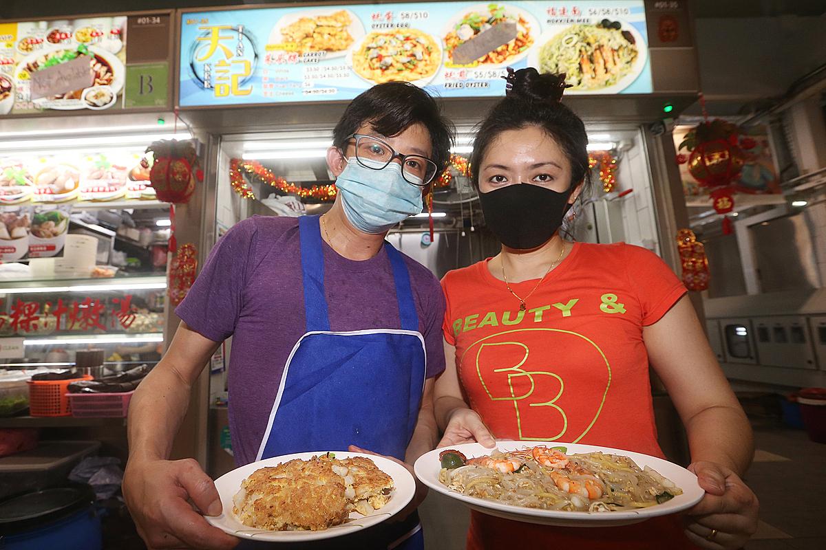 Ang và bạn đời với gian hàng ăn vặt vừa nhận được giải thưởng tôn vinh đóng góp cho văn hóa bán hàng rong của Singapore. Ảnh: Today.