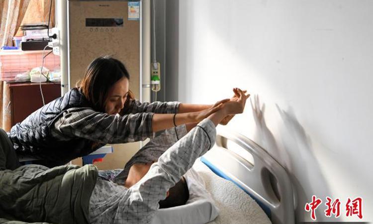 Lo lắng Bằng không vận động lâu ngày sẽ bị teo cơ nên ngày nào Lưu Ninh cũng xoa bóp, từ cánh tay đến hai chân cho người yêu. Ảnh: chinanews.