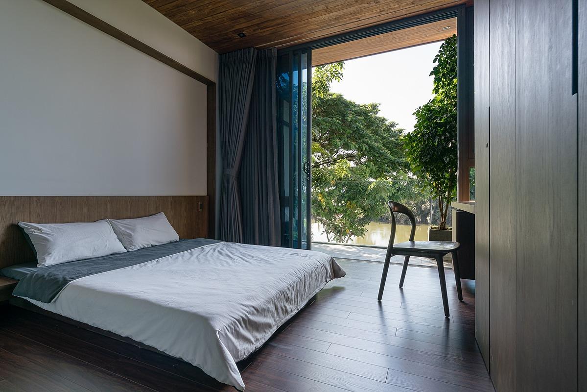 Phòng ngủ được bố trí ô cửa lớn để nhìn ra bờ sông phía trước nhà. Ảnh: Quang Trần.