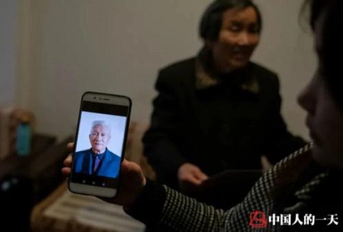 Cô gái chìa bức ảnh cha mình khi còn sống cho khách xem. Ảnh: Chinanews.