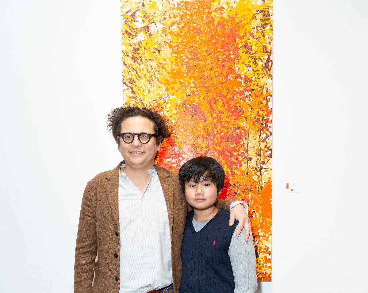 Xèo Chu cùng chủ phòng tranh George Berges trong triển lãm của cậu bé tại đây tháng 12/2019. Ảnh: Gia đình cung cấp.