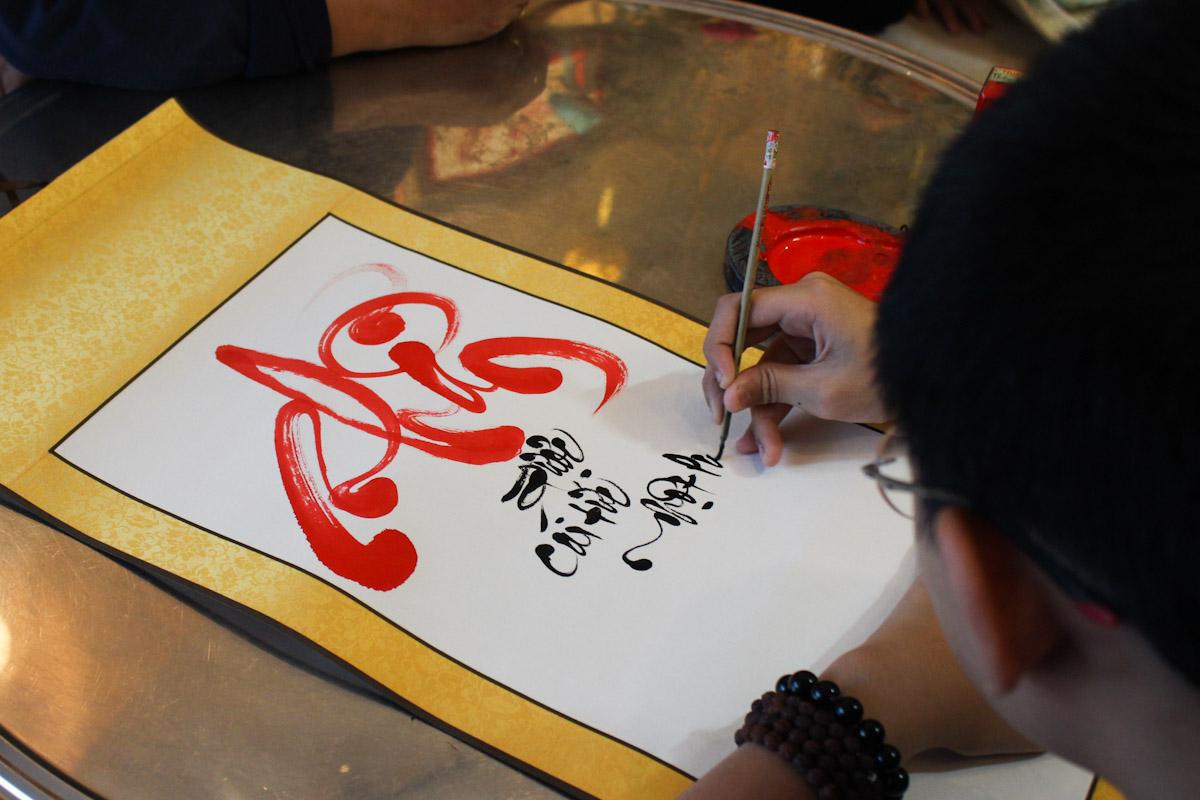 Mỗi dịp năm mới, Thiên Phú thường đến chùa cho chữ. Em có thể cho chữ hàng trăm người liên tục. Ảnh: Diệp Phan.