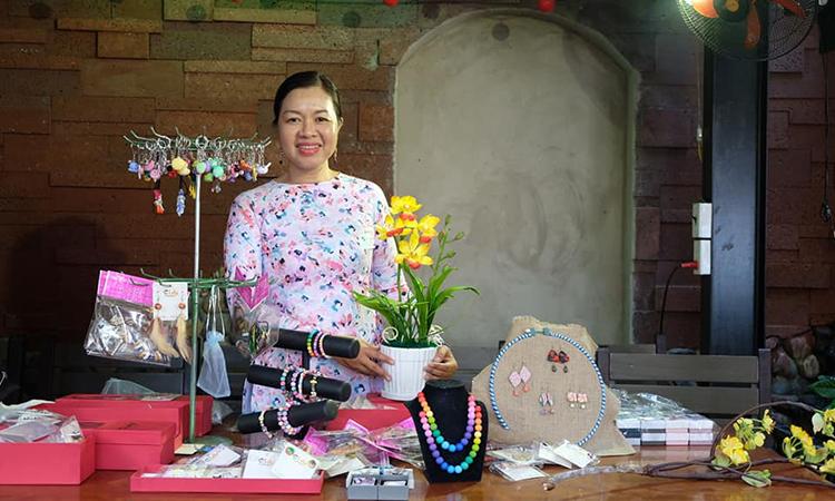 Chị Linh Vy bên các sản phẩm trang sức, móc khóa được làm bằng đất sét của mình.