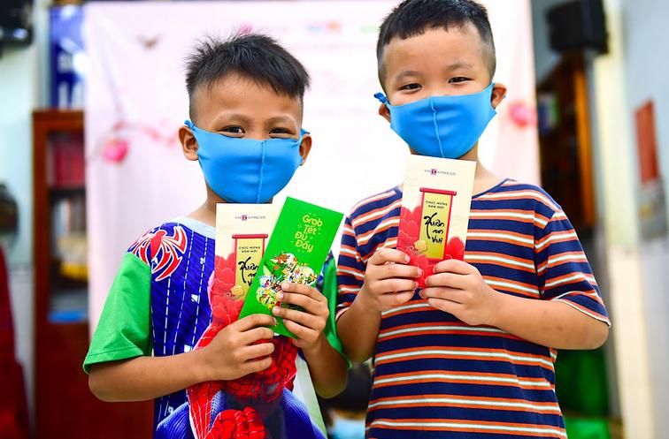 Minh Sang (trái) và Tấn Thi (phải) rất vui khi nhận bao lì xì. Hai bé hứa sẽ dùng số tiền này để mua thêm truyện đọc hoặc những dụng cụ hỗ học tập.