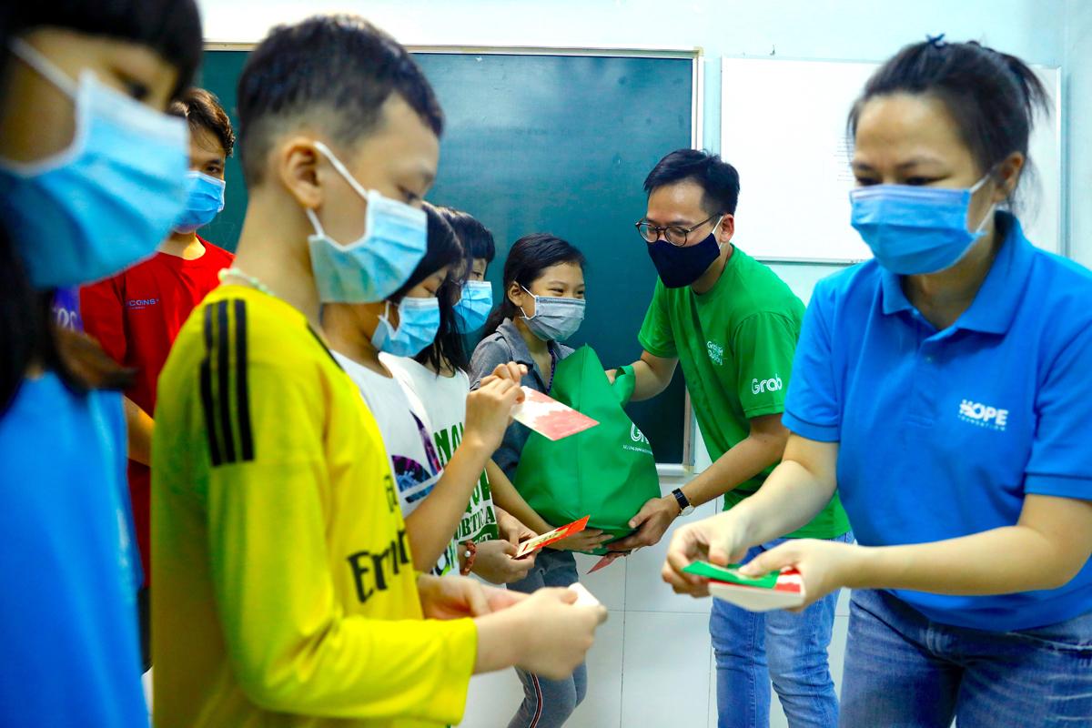Buổi chiều cùng ngày, chương trình tiếp tục đến Mái ấm La Vang, quận Tân Phú để trao hơn 100 phần quà Tết cho trẻ em cơ nhỡ đang được nuôi dưỡng tại đây. Đại diện Grab và Quỹ Hy Vọng đang trao từng bao lì xì Tết cho các em. Bé Minh Hùng (áo vàng) nói đã không ngủ trưa vì mong ngóng các cô, chú.