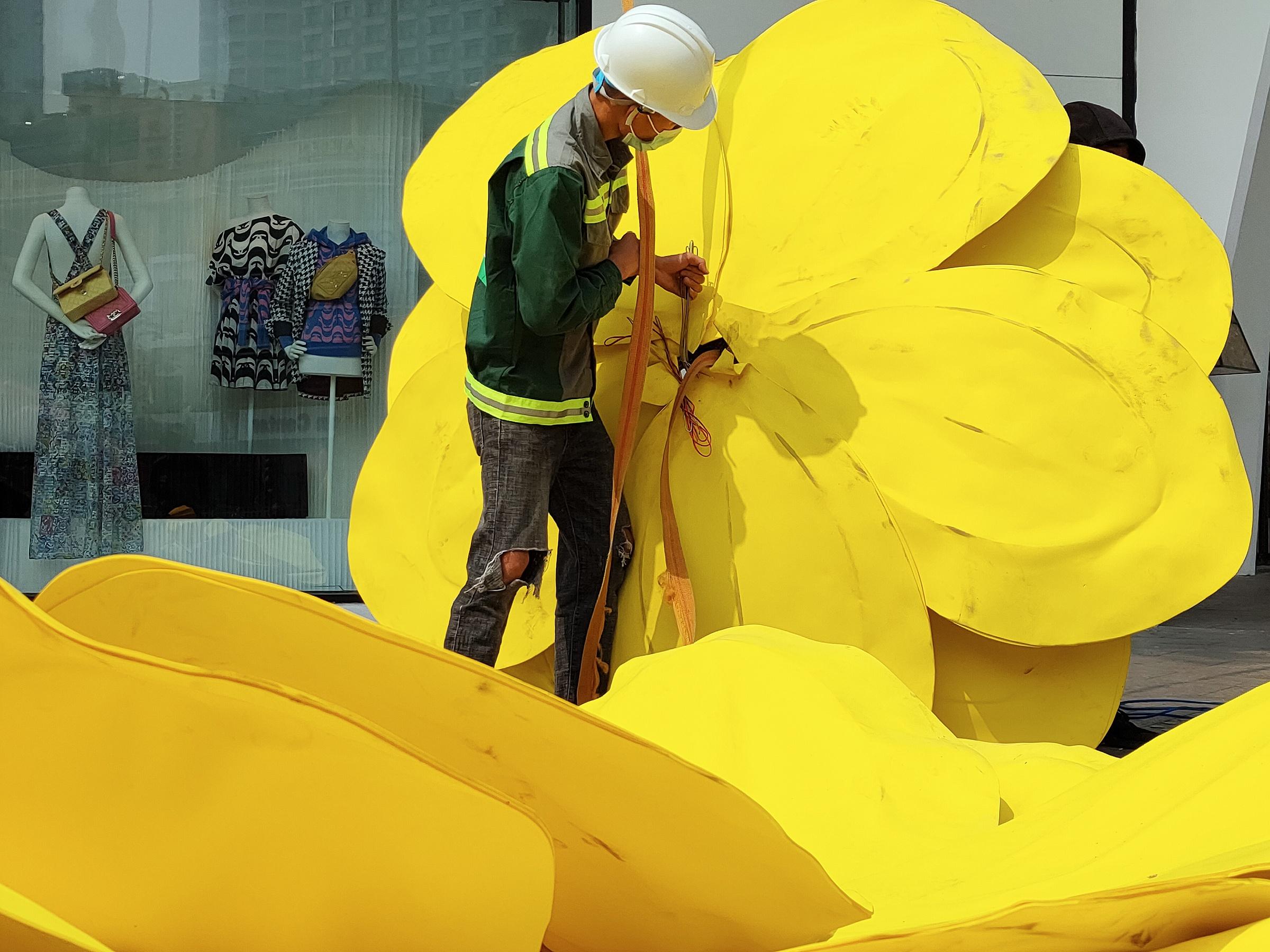 Giữa trưa nắng, đường phố thưa vắng người, những người thợ vẫn âm thầm làm việc. Họ treo những bông mai vàng với kích cỡ lớn lên một góc phố, khoác màu áo Tết lên những cung đường của thành phố khi năm mới sắp đến.