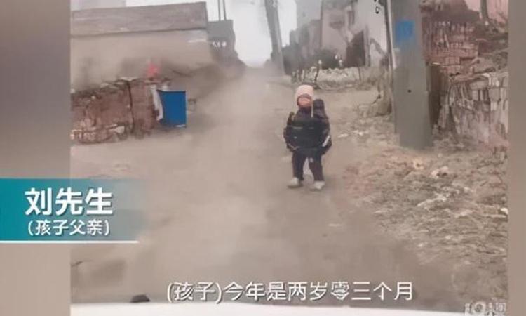 Cậu bé 2 tuổi đợi bố mẹ ở cổng làng tại thành phố Vĩnh Thành, tỉnh Hà Nam, Trung Quốc. Ảnh: kknews.