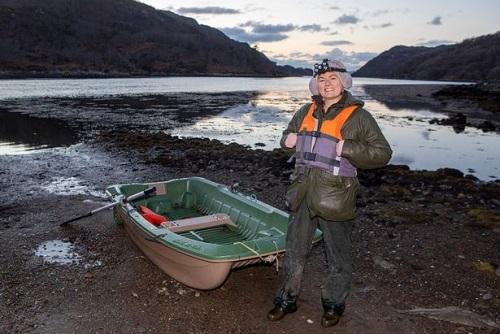 Chiều thuyền nhỏ giúp nữ nhân viên chăm sóc người già qua sông. Ảnh: SWNS.