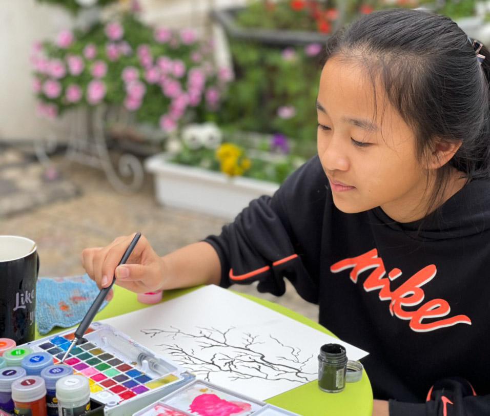Nguyệt Anh thường vẽ tranh trước sân nhà. Ảnh: Thanh Hiển.
