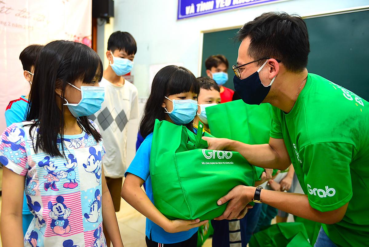 Bé Minh Anh khệ nệ ôm túi quà từ đại diện Grab.