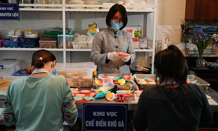 Đặng Thị Hương đang cùng những phụ nữ tại Hopebox chuẩn bị nguyên liệu để sản xuất ra những chiếc bánh cookies. Ảnh: VietnamAirlines.